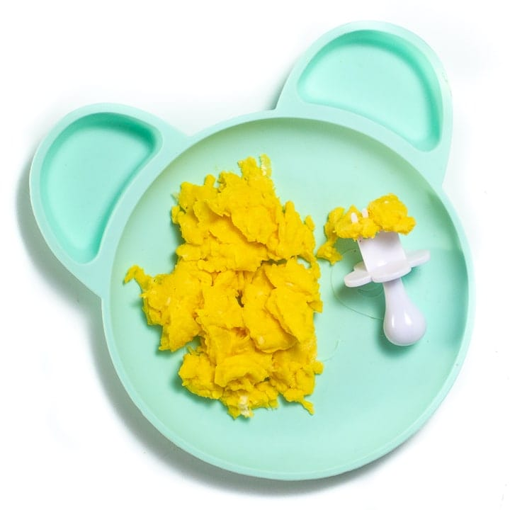 Blue baby plate full of soft scrambled eggs.