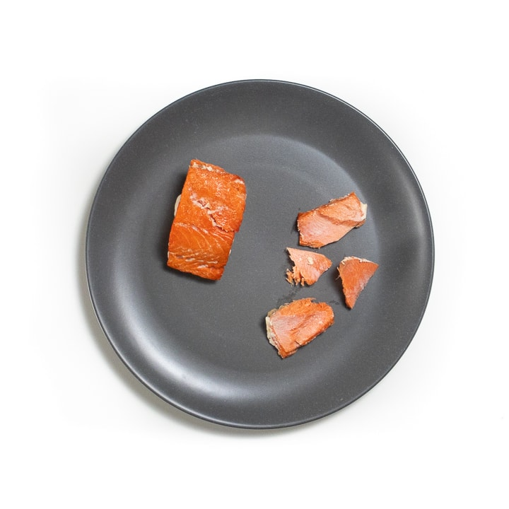 gray plate with cooked salmon for baby both for palmar and pincer grasps.