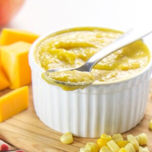 A small white bowl filled with a corn, squash and apple baby food puree.