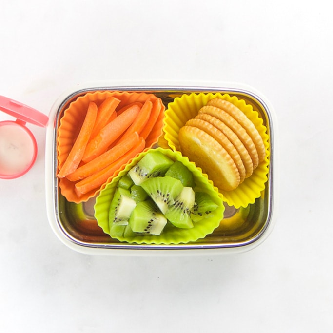 Rectangle kids bento box with healthy snacks for kids - 3 muffin molds filled with kiwi, carrot sticks and crackers. On the side is a small pink container filled with ranch dressing.