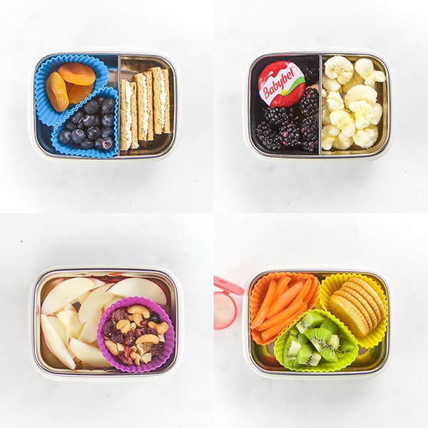 4 snack boxes on a white background with silver bentos on top. each box has a selection of healthy kid snacks inside.