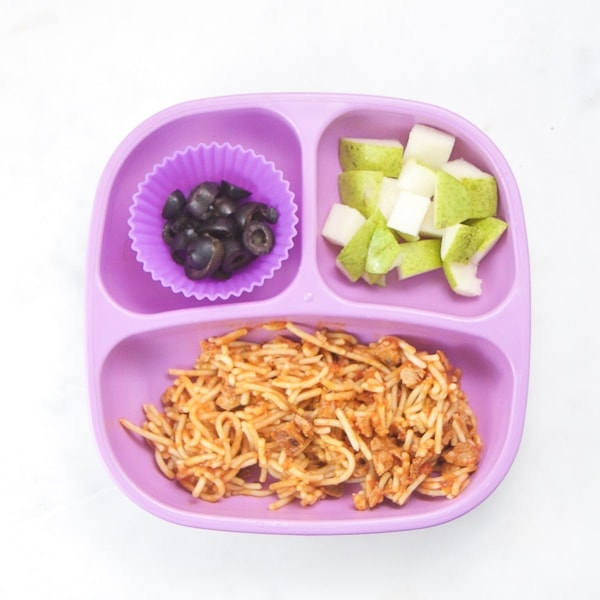 toddler dinner plate with cut up pasta, fruit and olives