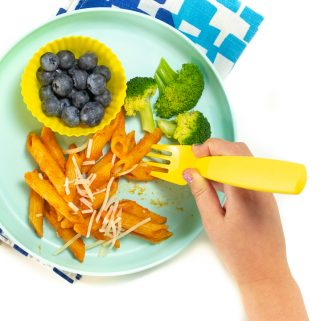 Small kids hands eating off a plate with hidden veggie pasta sauce with pasts, blueberries and broccoli.