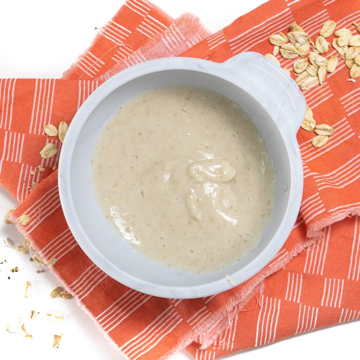 Gray baby bowl filled with pureed oatmeal cereal.