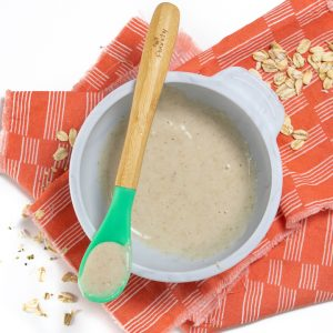 Bowl of oatmeal for baby with spoon resting on top of gray bowl.