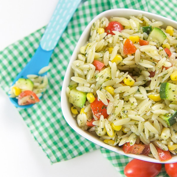 A bowl of baby led weaning orzo pesto pasta with vegetables.