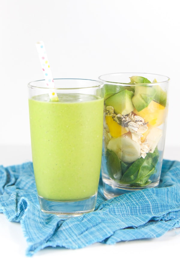 Baby friendly green spinach smoothie in a glass with a separate glass filled with whole smoothie ingredients.
