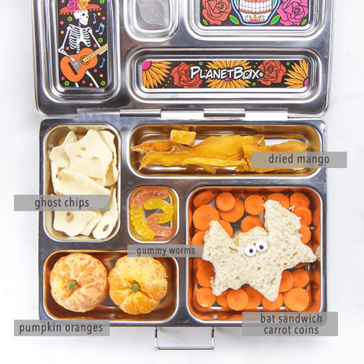 Image is of an open lunch box with healthy halloween themed food inside with everything labeled.