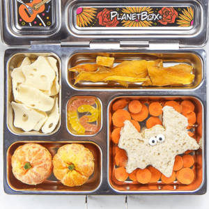 Image is of an open lunch box with healthy halloween themed food inside.