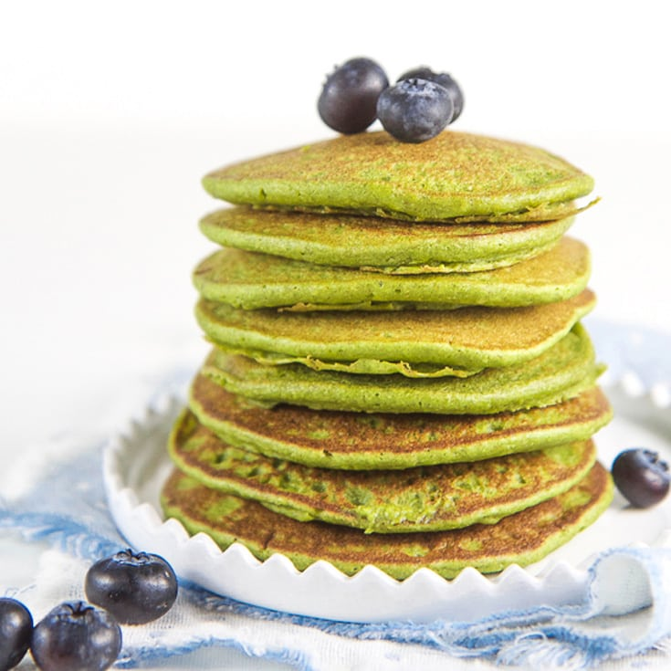 A stack of healthy gluten free blender spinach pancakes topped with fresh blueberries.
