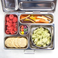 silver planetbox bento box filled with avocado chicken salad, crackers, raspberries, carrots and dye-free candy.