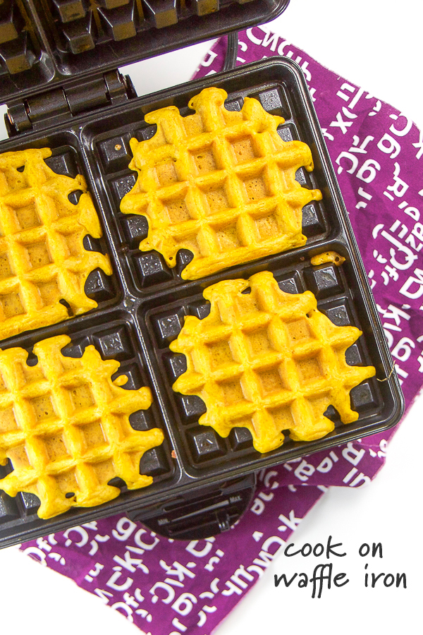 Golden milk waffles cooking in a waffle iron.