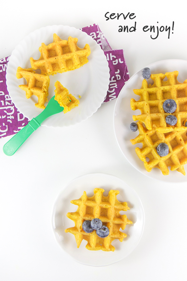 Golden milk waffles on white plates with fresh blueberries.