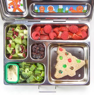 A silver lunch box filled with holiday themed foods for kids.