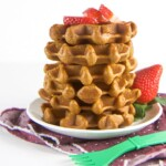A stack of healthy gingerbread waffles on a white plate with fresh strawberries.