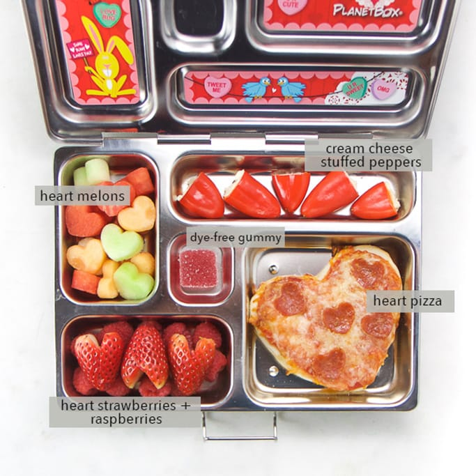 Image is of a school lunch box with valentine themed food inside.