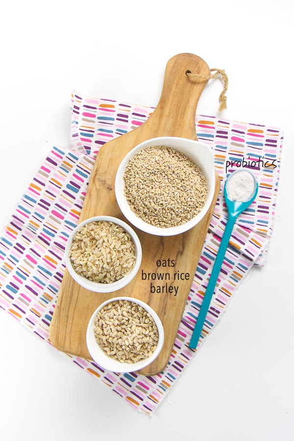 layout of what is in the homemade baby cereal - small white bowls on top of a wood cutting board filled with dry oats, brown rice and barley. On top of a multi colored napkin is a spoon filled with probiotics