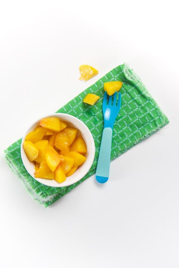 small white bowl on green napkin - finger food of peaches fill the bowl. fork on napkin with a chunk in it.