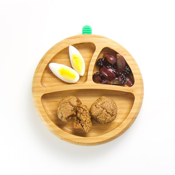 baby-led weaning breakfast on wooden plate with 3 sections - mini muffins, cut hard boiled egg, grapes and blackberries