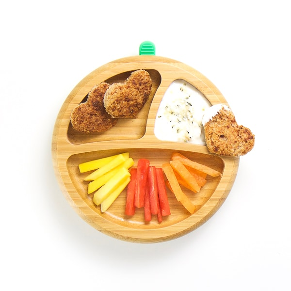 finger food breakfast on wooden plate with 3 sections - strips of mango, watermelon and cantaloupe with heart shaped cinnamon toast, yogurt with coconut and hemp seeds for dipping