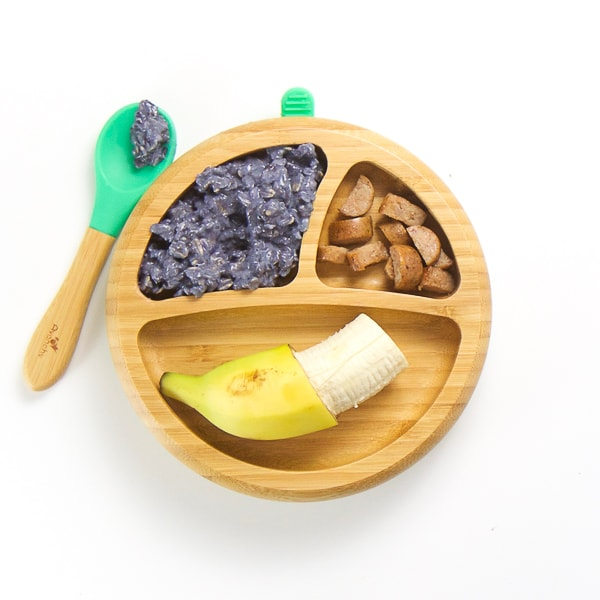 finger food breakfast on wooden plate with 3 sections - banana with end of peel still attached, blueberry oatmeal with spoon on the side of plate and chicken apple sausage cut into small chunks