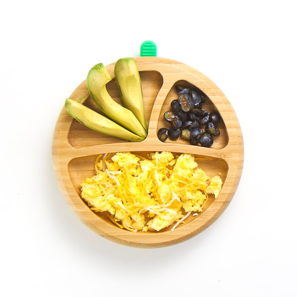 baby-led weaning breakfast on wooden plate with 3 sections - cheesy scrambled eggs, avocado wedges and cut blueberries