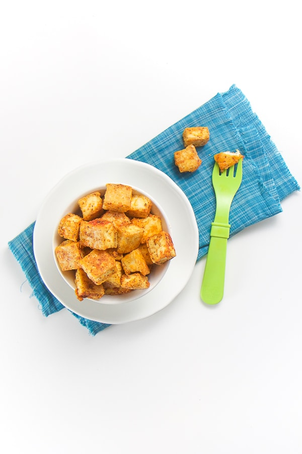 finger food - white bowl filled with cubes of seasoned tofu onto of a blue napkin.