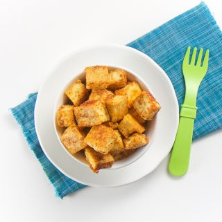 baby-led weaning nuggets - small white bowl on top of blue napkin that is filled with seasoned tofu chunks