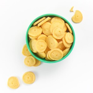 small green bowl filled with round cheese crackers, some are spilling onto the white surface.