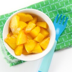 baby-led weaning warm peaches finger food for baby or toddler - small white bowl on top of green napkin with a blue fork. Inside of bowl are chunks of peaches with a sprinkle of nutmeg.