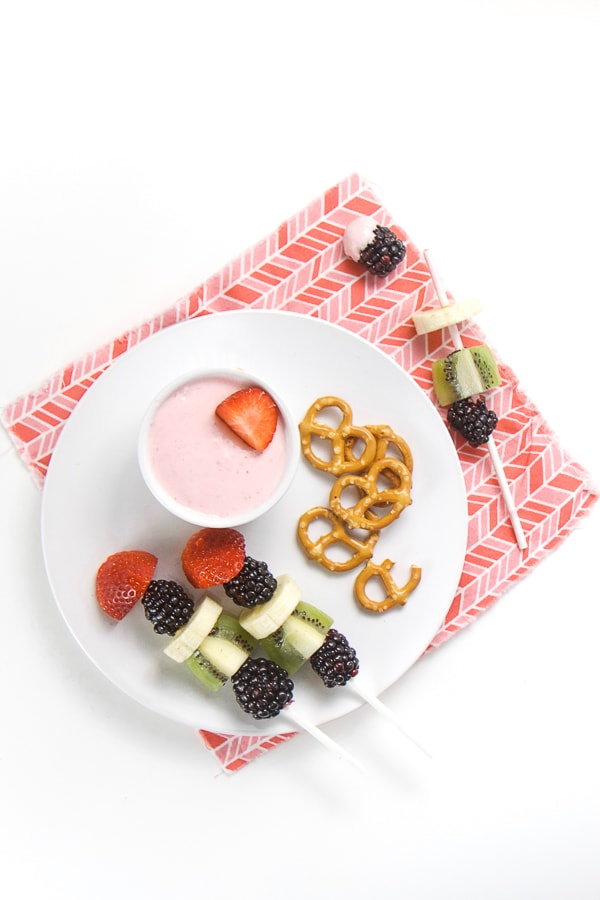 white plate with a small bowl of pink strawberry cream cheese dip and along with 2 fruit kabobs with strawberry, banana, kiwi and blackberry as well as a small pile of pretzels. All on top of a pink napkin.