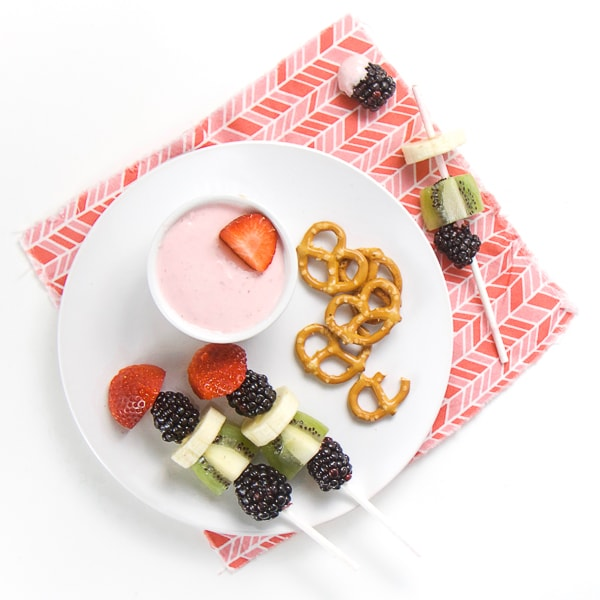 round white plate on pink napkin, small while bowl on plate filled with strawberry cream cheese dip, fruit kababs and a small handful of pretzels