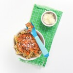 small white bowl filled with baby led weaning pasta with Bolognese sauce on top. Bowl has blue fork with pasta sitting on top of bowl.