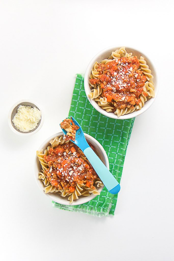 2 white bowls filled with pasta and bolognese sauce, sitting on top of a green napkin. Small bowl of parmesan sits off to the side. Blue fork in sitting on top of one of the bowls with pasta on it - great finger foods for baby