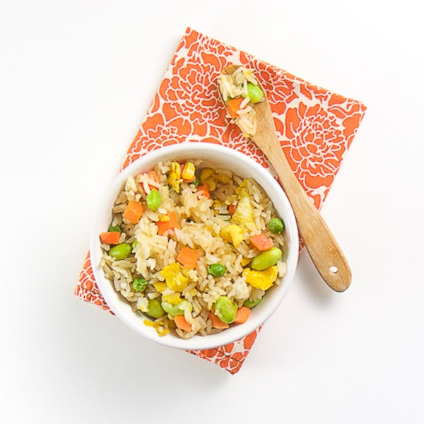 white bowl filled with brown rice, veggies and chunks of scrambled egg. white bowl is sitting on an orange napkin with flowers on it.