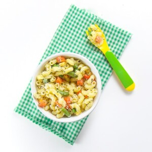 small white bowl filled with pasta and vegetables. Sits on top of a green and white checkered napkin with a green and yellow fork filled with pasta
