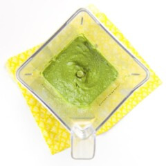baby puree recipe - a blender is sitting on top a yellow napkin. Inside blender is a smooth green puree