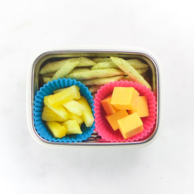 Rectangle kids bento box with healthy snacks for kids - snapeas crackers and 2 muffin molds filled with cut cheddar cheese and pineapple sections