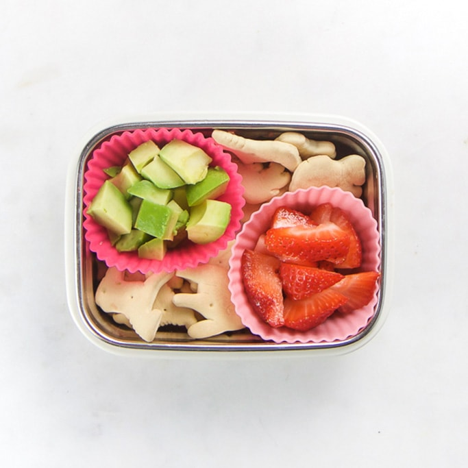 Rectangle kids bento box with healthy snacks for kids - animal crackers and 2 muffin molds - 1 filled with chunks of avocado and the other filled with cut strawberries