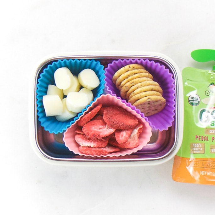 Rectangle kids bento box with healthy snacks for kids - 3 muffin molds filled with cut string cheese, crackers and dried strawberries. On the side is an applesauce pouch