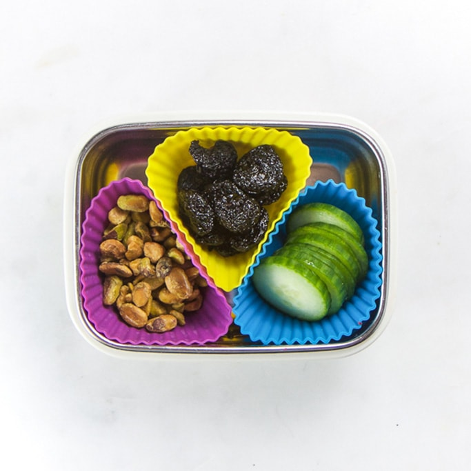 Rectangle kids bento box with healthy snacks for kids - 3 muffin molds filled with pistachios, dried fruit and cut cucumber.