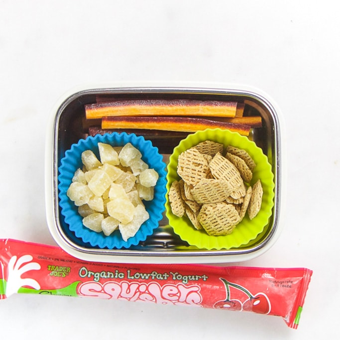 Rectangle kids bento box with healthy snacks for kids - cut purple carrots, dried pineapple and dried cereal and on the side is a frozen yogurt tube.