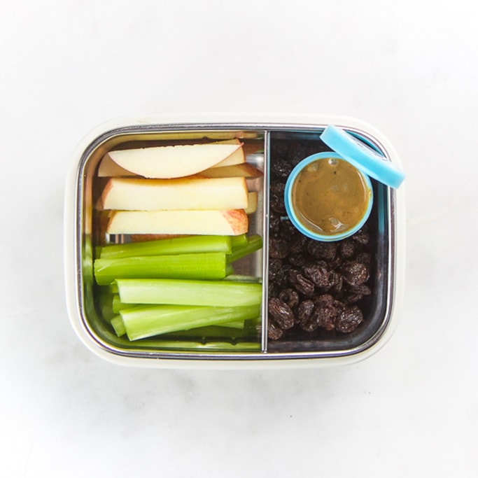 Rectangle kids bento box - cut up apples and celery, small blue container with peanut butter and some raisins