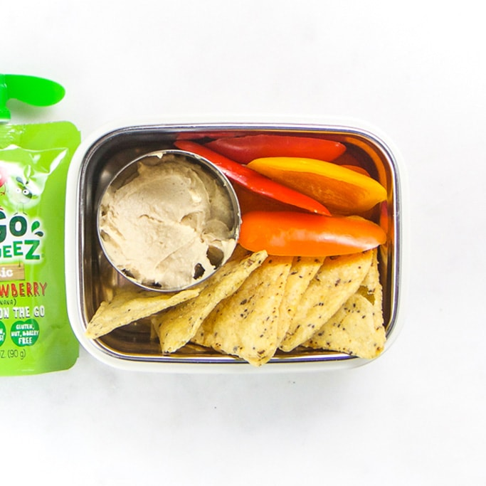 Rectangle kids bento box - small round container with hummus, cut bell peppers, grain chips and an apple pouch sitting off to the side.