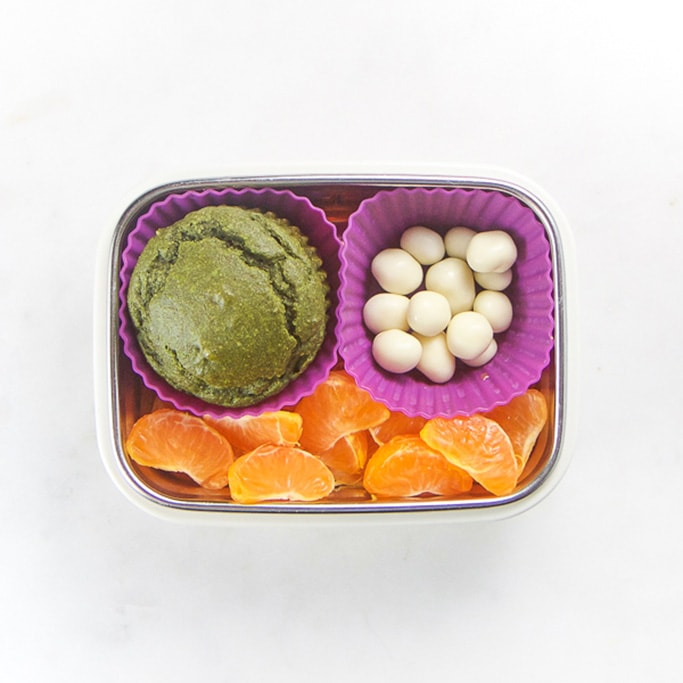 Rectangle kids bento box - green muffin, yogurt covered raisins, mandarin oranges sections.