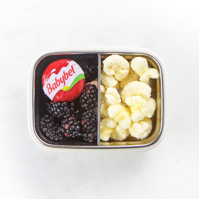 Rectangle kids bento box with healthy snacks for kids - black berries, a babybel cheese circle and half of the container filled with cheese puffs.