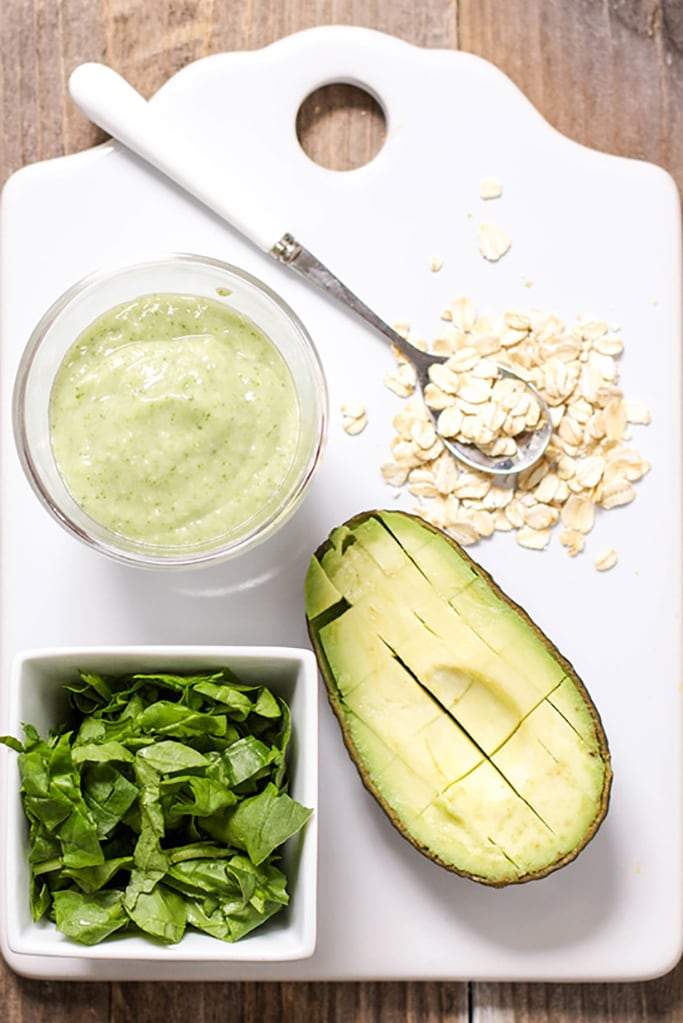 White cutting board with old fashioned oats, and cut avocado and small square bowl filled with chopped spinach. At the top left if a clear bowl filled with a healthy baby food puree.