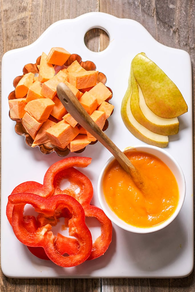 White cutting board with a small silver bowl filled with chopped sweet potato, slices of pear and slices of red pepper piled next to each other. In the bottom right is a small bowl with a wooden spoon inside that has a smooth homemade baby food puree.