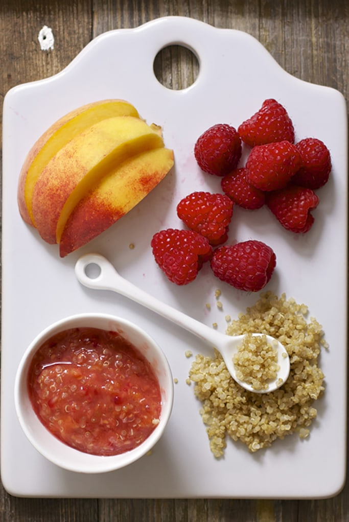 White cutting board with slices of peaches, whole raspberries and cooked quinoa piled on top. There is a small white bowl with the final chunky baby food puree inside.