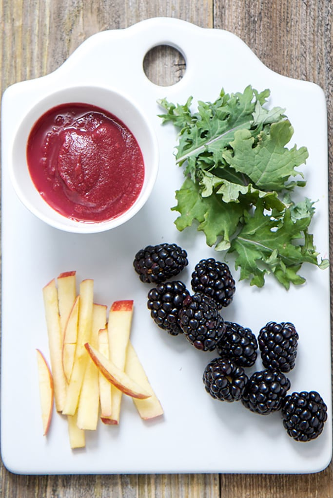 White cutting board with apple slices, blackberries and baby kale scattered on top. There is also a small white bowl in the corner with the finished baby puree.